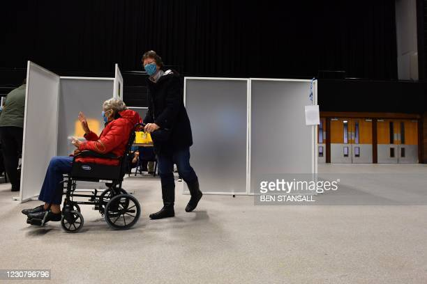 Patient is pushed in a wheelchair inside the Covid-19 vaccination centre set up inside Brighton Centre in Brighton, southern England, on January 26,...