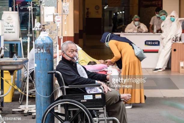 Patient is seen in a wheel chair outside Bekasi Public hospital with an oxygen mask and tank. Hospitals in Java, Indonesia are shifting medical...