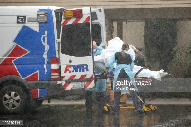 A patient is shielded as they are put into an ambulance outside the Life Care Center of Kirkland on March 7 2020 in Kirkland Washington Several...