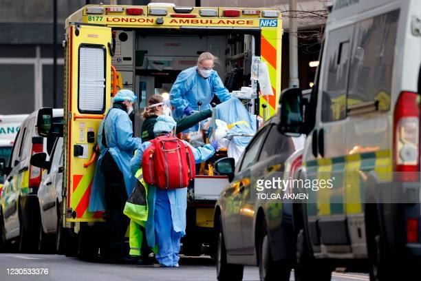 Patient is taken from an ambulance by staff wearing PPE equipment at the Royal Free Hospital in London on January 11, 2021 as surging cases of the...
