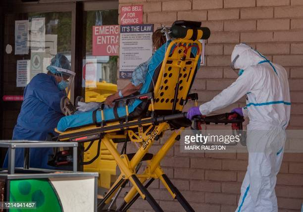 Patient is taken from an ambulance to the emergency room of a hospital in the Navajo Nation town of Tuba City during the 57 hour curfew, imposed to...