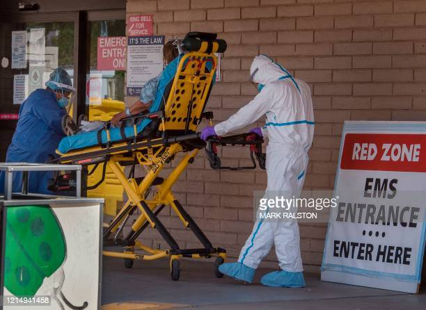 A patient is taken from an ambulance to the emergency room of a hospital in the Navajo Nation town of Tuba City during the 57hour curfew imposed to...