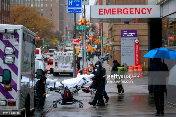 Patient is transported outside of Tisch Hospital in New York on November 13, 2020. - Bars and restaurants in New York will shut early on November 13...
