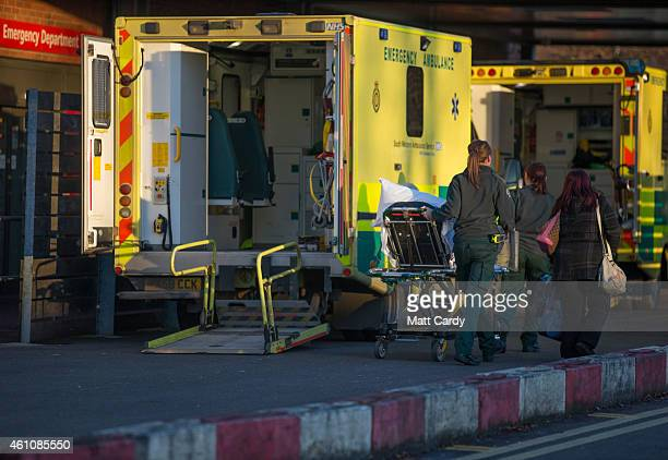 A patient is wheeled from a ambulance parked outside the Accident and Emergency department of Gloucestershire Royal Hospital on January 6 2015 in...