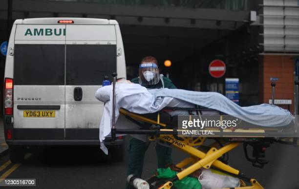 Patient is wheeled from an ambulance into the Royal London hospital in London on January 10, 2021 as surging cases of the novel coronavirus are...