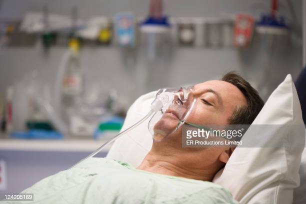 patient laying in hospital bed with oxygen mask - breathing device stock pictures, royalty-free photos & images