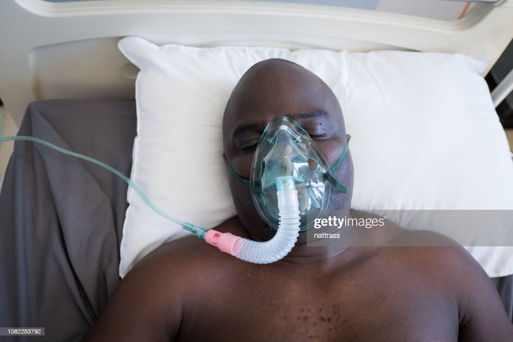 Patient lies in hospital bed on a respirator : Stock Photo