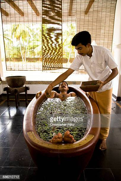 A patient lies near fully submerged in a wooden tub of herb infused water for promote relaxation during the process of detoxification as part of the...