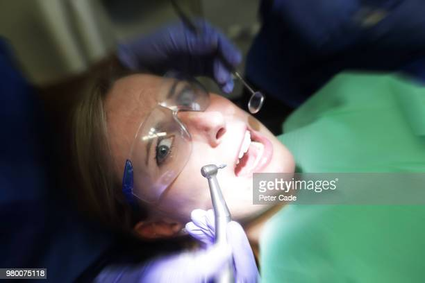 patient looking scared in dentist chair - dental fear stock pictures, royalty-free photos & images
