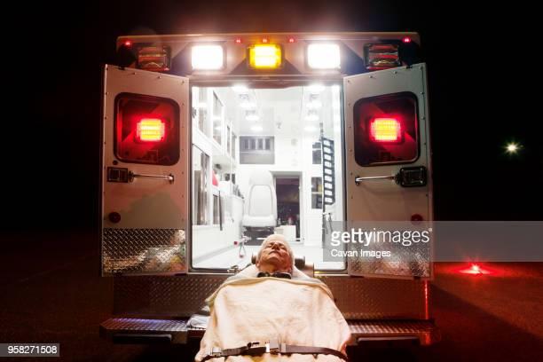 Patient lying on hospital gurney by ambulance