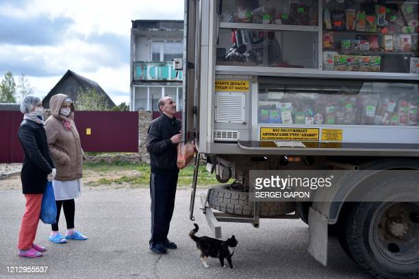Patient of a social shelter buys food from a truck transformed into a mobile shop in the village of Kreva, some 100 km northwest of Minsk, on May 14...