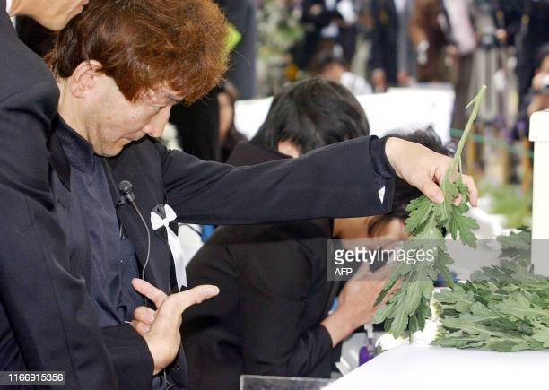 A patient of Minamata disease caused by mercury poisoning places a chrysanthemum on an altar at the 50th anniversary of one of the worst health...