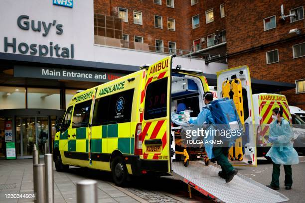Patient on a gurney is taken from an ambulance parked outside Guy's Hospital in London on December 29 as a new strain of the coronavirus appears to...