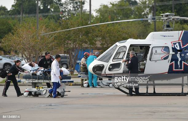 A patient on a stretcher is transfered into a helicopter which departed from the Baptist Beaumont Hospital in Beaumont Texas on August 31 2017 / AFP...