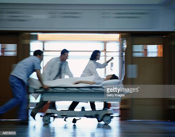 patient on stretcher rushed through hospital by medical staff - hospital gurney stock pictures, royalty-free photos & images