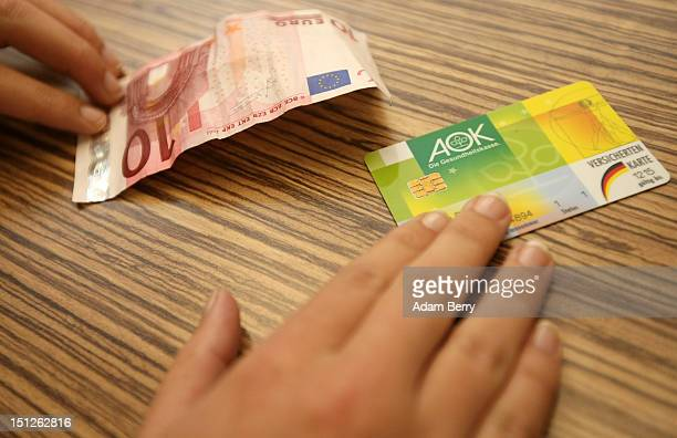 A patient pays a quarterly consultion fee while handing over her Allgemeine Ortskrankenkasse health insurance card on September 5 2012 in Berlin...