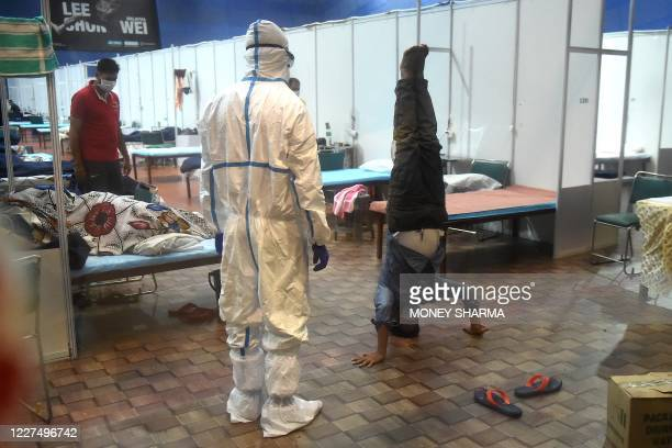 A patient performs yoga as a doctor wearing a Personal Protective Equipment suit watches him inside a ward at the Commonwealth Games Village sports...