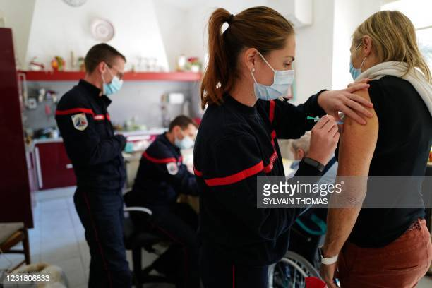Patient receives a dose of the Pfizer-BioNTech Covid-19 vaccine by a firefighter, at her home in Les Matelles, southern France, on March 19, 2021. -...