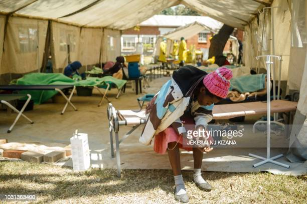 A patient receives a medication by intravenous inside a cholera treatment tent during a visit of Zimbabwe Minister of Health at the cholera treatment...