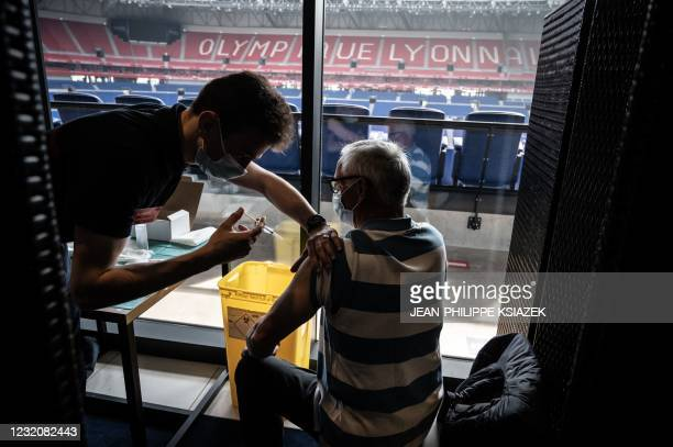 Patient receives an injection of the Moderna Covid-19 vaccine on the opening day of a mass vaccination centre set up in the OL Group's Groupama...
