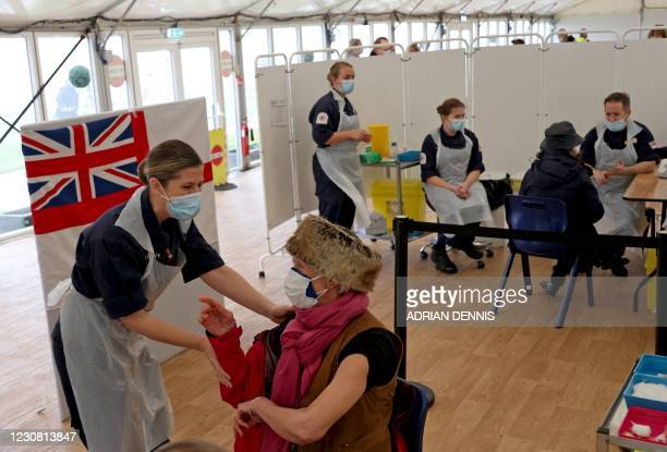Patient receives an injection of the Oxford/AstraZeneca Covid-19 vaccine by Royal Navy medics at a vaccination centre set up at Bath racecourse in...