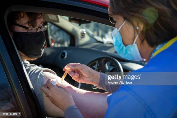 Patient receives their first dose of the COVID-19 AstraZeneca Oxford vaccine in their arm while attending the drive through vaccination centre in the...