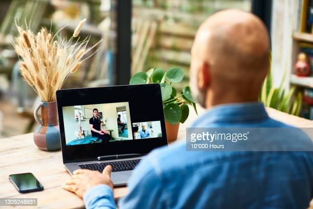 patient receiving advice on laptop from physical therapist - patient stock pictures, royalty-free photos & images