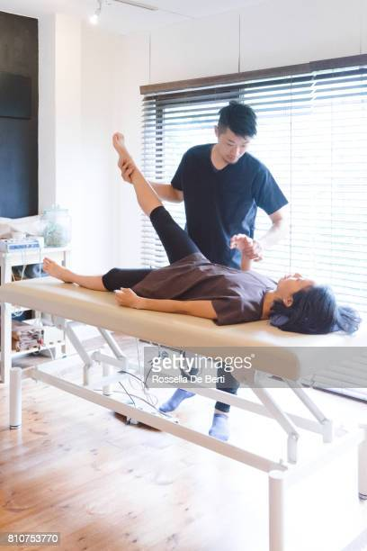 patient receiving chiropractic treatment - osteopath stock photos and pictures
