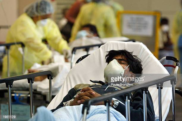 A patient rests after testing in the Severe Acute Respiratory Syndrome screening area at the Tan Tock Seng Hospital April 25 2003 in Singapore The...