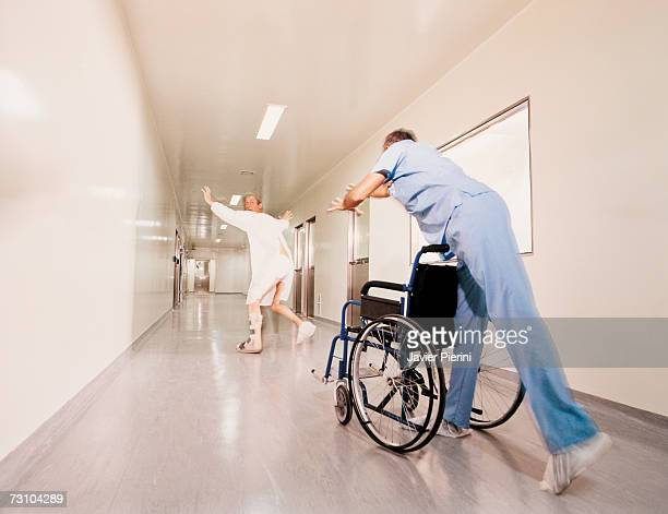 Patient running from wheelchair and medical stafff, rear view