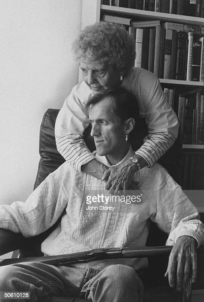 AIDS patient Ryland Jones chatting w his nurse mom Ida as she stands behind the chair he is sitting in w her arms around his neck they are both...