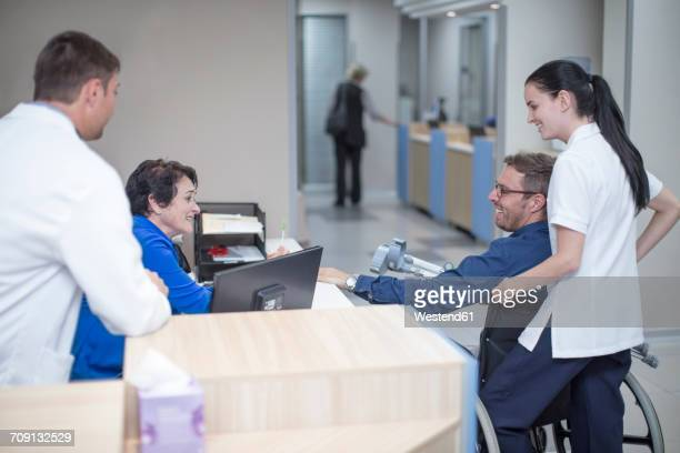 Patient siting in wheel chair talking to staff at the reception