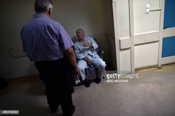 A patient sits in a corrdior of an Athens hospital on July 8 2015 With expectations of a Greek exit from the eurozone gathering pace health officials...