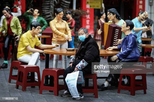 Patient sits nearby to a sculpture in a traditional food culture street on February 8, 2020 in Wuhan, Hubei province, China. The number of those who...
