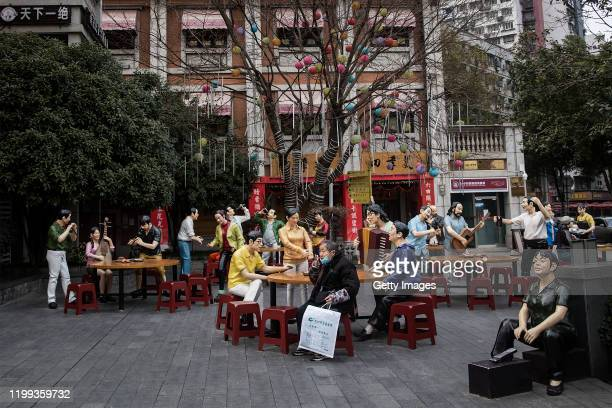 A patient sits nearby to a sculpture in a traditional food culture street on February 8 2020 in Wuhan Hubei province China The number of those who...