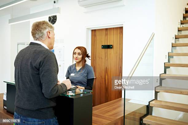 Patient standing at the reception desk in a dental clinic