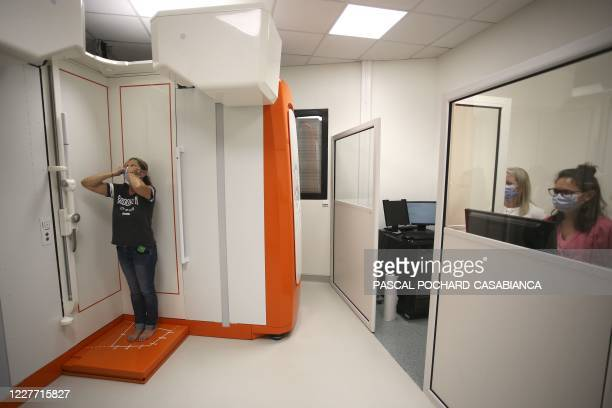 A patient stands during a full body radiography made by the new EOSedge 3D Imaging system at the Madonuccia radiography center on July 20 in Ajaccio...