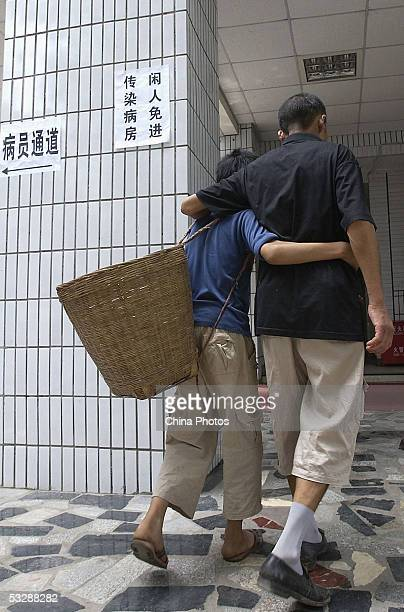Patient suffering from a mysterious disease, supported by a young boy, walks to the infection wards at the Ziyang First People's Hospital on July 26,...