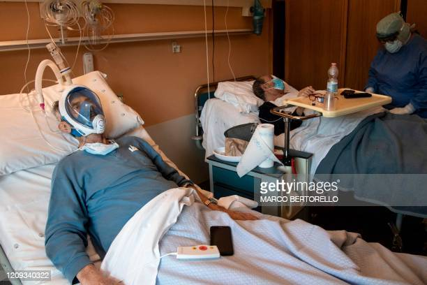 A patient suffering from COVID19 who uses the Decathlon snorkeling face mask lays in a bed in the COVID19 ward of the Maria Pia Hospital in Turin on...