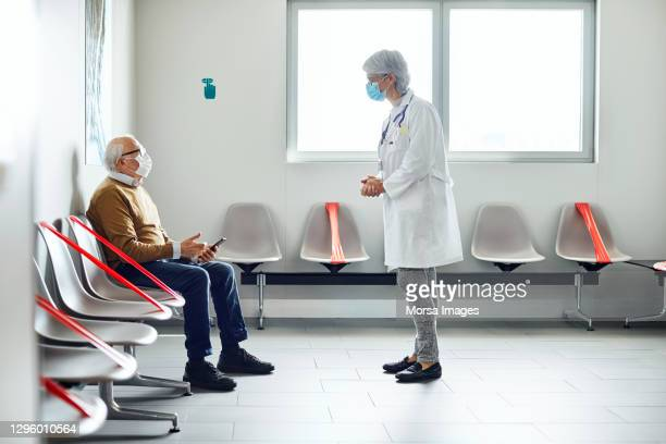 patient talking with doctor in waiting room - outpatient care stock pictures, royalty-free photos & images
