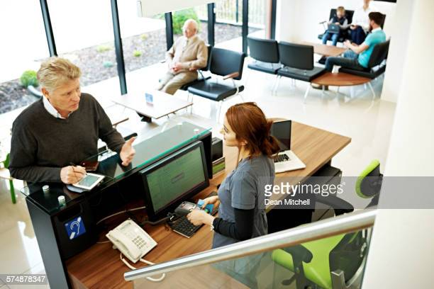 patient talking with receptionist at dental clinic - receptionist stock pictures, royalty-free photos & images