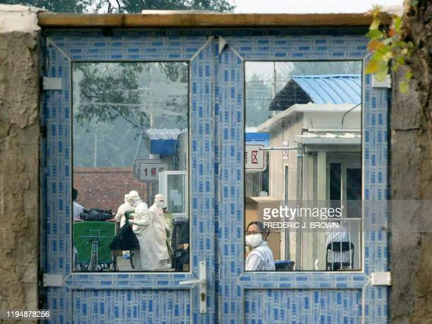 A patient under quarantine at the Xiaotangshan Severe Acute Respiratory Syndrome hospital looks back through a reardoor entrance 07 May 2003 on the...