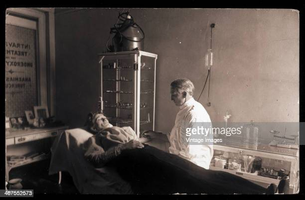 A patient undergoes a procedure in the intravenous treatment room of a clinic circa 1890