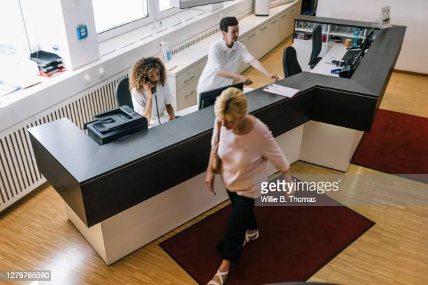 patient walking away from mri clinic reception - medical receptionist uniforms stock pictures, royalty-free photos & images