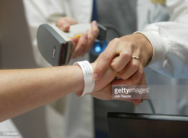 A patient wears a bar code on a wrist so a doctor can pull up medical information during a demonstration of the IDX wireless Carecast health...