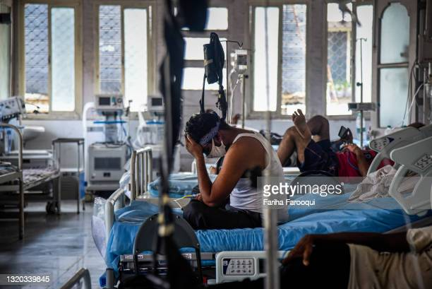 Patient who has Covid-19 sits on his bed in an ICU ward at the government-run St. George hospital on May 27, 2021 in Mumbai, India. India's prolonged...