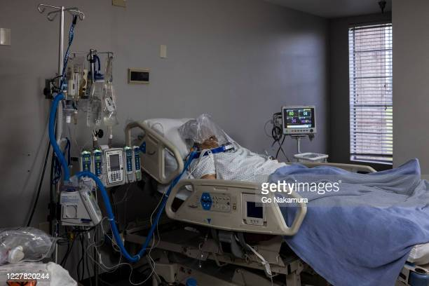 Patient who is treated with a helmet-based ventilator lies on a bed in the COVID-19 intensive care unit at the United Memorial Medical Center on July...
