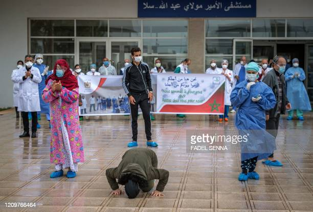 Patient who recovered from the Covid-19 disease caused by the novel coronavirus kisses the ground as another rejoices with the medical staff as they...