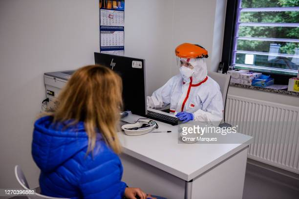 Patient who suspects of possibly being infected with coronavirus speaks with a doctor before performing a COVID 19 swap test at the Krakow University...
