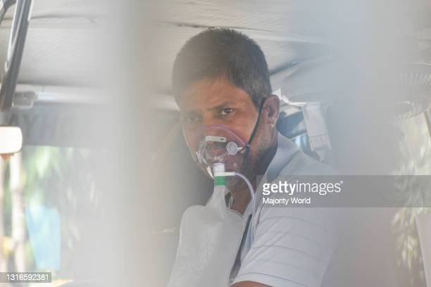 Patient who tested positive for COVID-19 waits wearing an oxygen mask to get admitted to a COVID care hospital. India has recorded the highest...